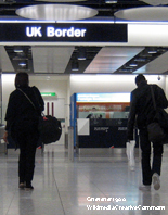Man and woman in silhouette seen from behind approaching the UK border at Heathrow Airport
